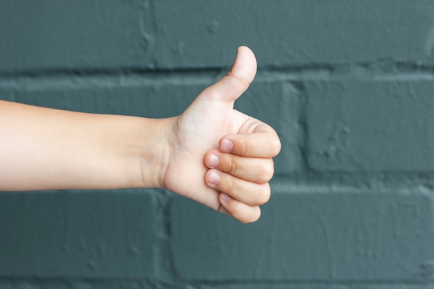 Child showing thumbs up on background of grey brick wall