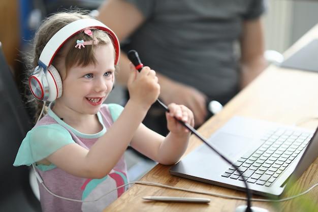 子供はヘッドフォンで椅子に座り、両手でマイクを持ちます。