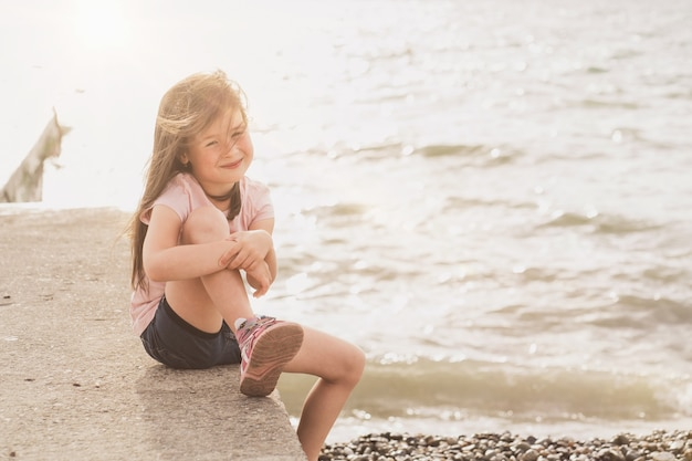 The child sits by the sea and enjoys the sunset a place for a text about children a cheerful girl en...