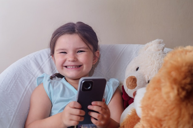 The child sits in a chair with toys bears and plays on the phone
