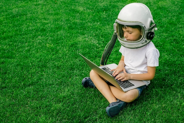 A child sits on the grass in an astronaut's helmet and studies on a laptop online enjoying nature.