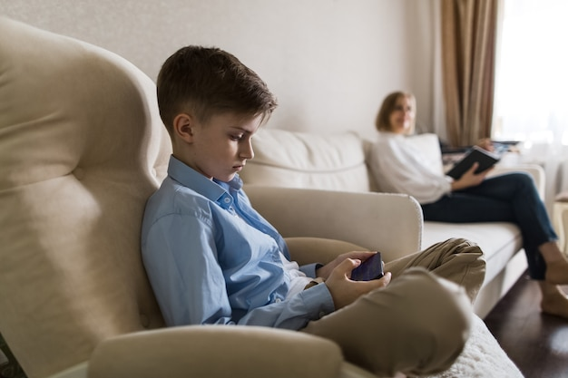 Ребенок сидит в кресле, смотрит в телефон