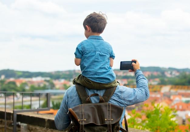Ребенок сидит на плечах отца во время прогулки по улицам старого города