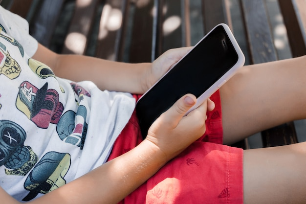The child sits in the park on a bench with a gadget. children use gadgets. a boy plays a game on a mobile phone.