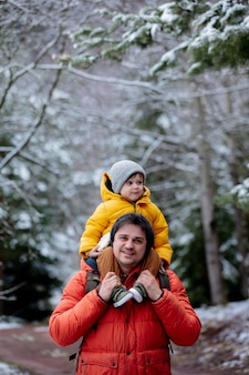 Child sits on the shoulders of his father during a walk by a frozen forest