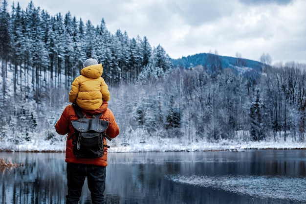 Child sits on the shoulders of his father during a walk by a frozen lake in the forest