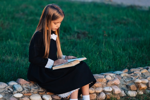 A child sits on a stone fence and reads a book.