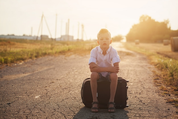 The child sits on a suitcase in the summer sunny day, the traveler