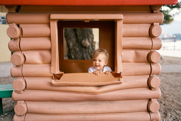 Child sits in a toy house near the window on the playground