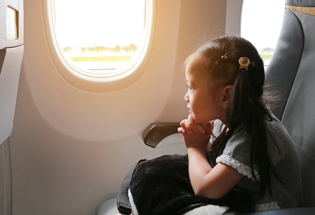 Child sitting by aircraft with praying near the window.