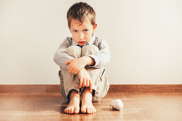 Child sitting on the floor barefoot with sad face for not being able to put on his clothes.