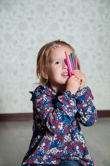 Child sitting on the floor and covers her face by crayons.