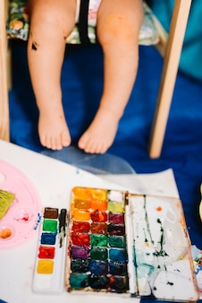 Child sitting near water colors and paper