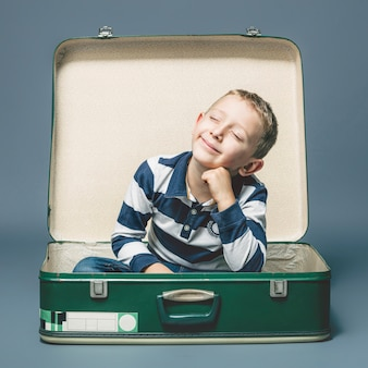 Child sitting in an old suitcase smiles imagining a journey