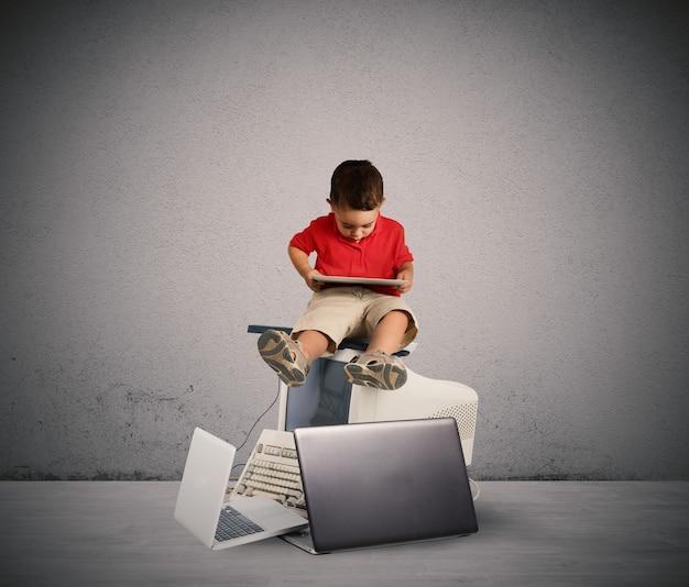 電子機器の山に座る子供