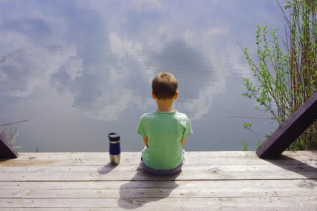 水の近くの木製の桟橋に座っている子供。川で一人の少年。