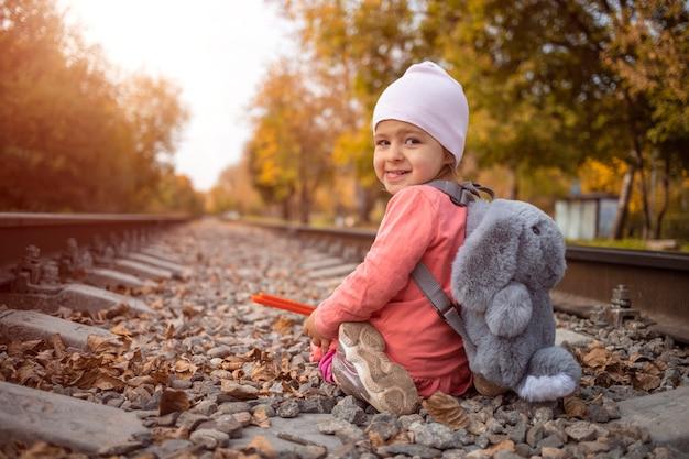 그날 태양의 마지막 광선을 잡는 버려진 철도 라인에 앉아 아이.