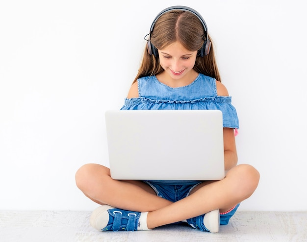 ラップトップで勉強している床に座っている子供