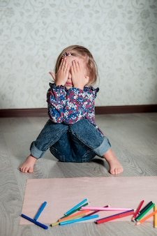 クレヨンと紙の近くの床に座っている子。小さな女の子の描画、絵画。創造性の概念。幸せ、笑顔。