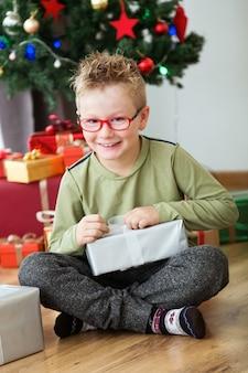 Ребенок, сидя на полу открытия подарок