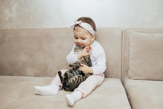 ソファに座ってぶち猫を抱きしめる子供