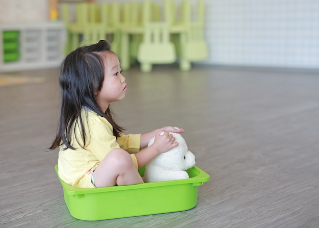 Child sitting in plastic tray playing at playroom