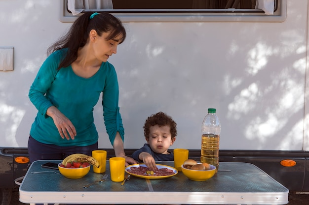 Child sitting at the table next to the camper while his mother serves snacks on a camping day