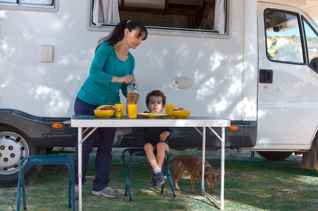 Child sitting at the table next to the camper, while his mother serves snacks and drinks on a camping day.