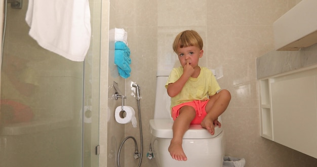 Child sitting toilet with thoughtful look picks his nose