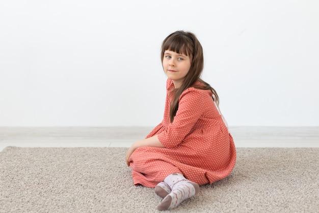 Ребенок сидит в скромном длинном розовом платье у белой стены