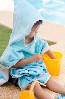 Child sitting with a hooded towel playing with a plastic bucket and an orange juice in a pool