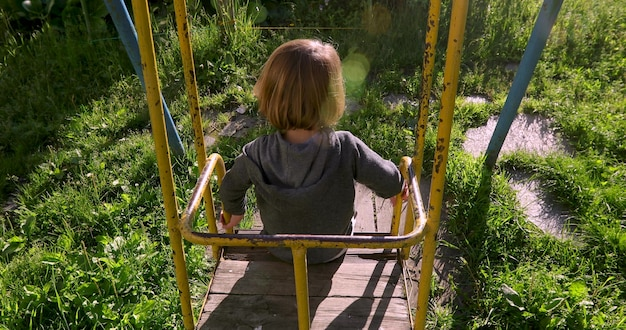 Child sitting in yard on old swing