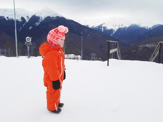 A child in ski outfit looks at a mountain slope in a ski resort view aside to the valley