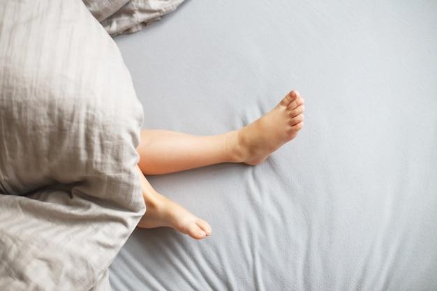Ребенок спит в постели. ножки ребенка торчат из-под одеяла