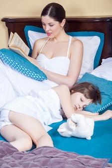 Child sleeping, mom read book. studio shot