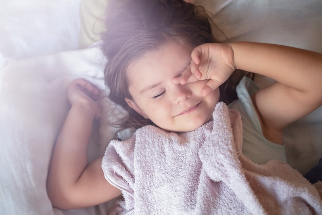 The child sleeps on the bed rubbing her eyes
