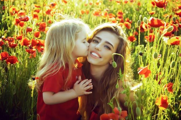 어머니 또는 여동생에서 자식 작은 소년 양 귀 비 필드에서 키스.