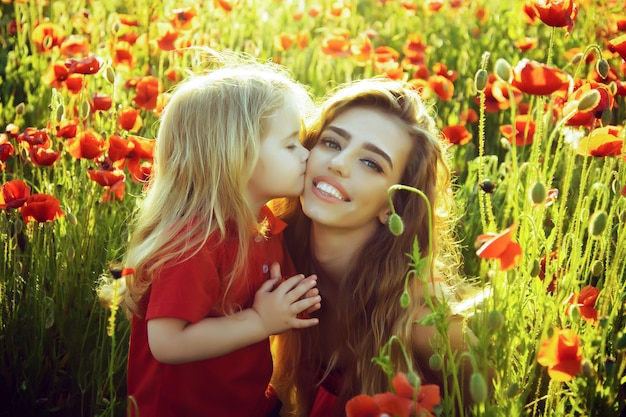 Child small boy at mother or sister kissed in poppy field.