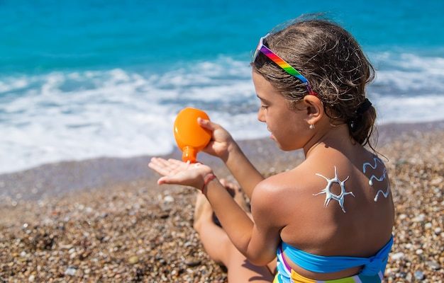 The child smears sunscreen on her back. selective focus. kid.