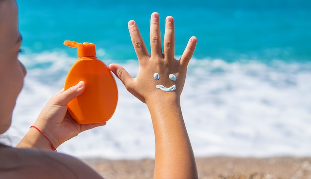 The child smears sunscreen on her hand. selective focus. kid.