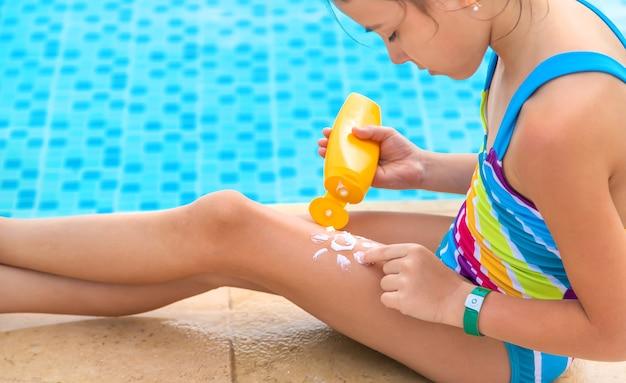子供は彼女の足に日焼け止めを塗ります。
