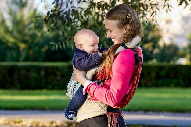 Ребенок улыбается в слинге в руках матери во время прогулки в парке