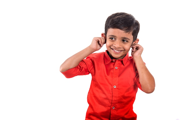 A child smiling and pulling his ears on a white space