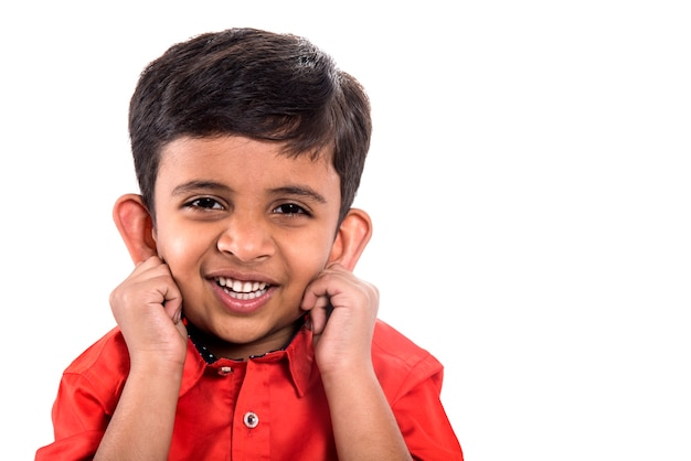 A child smiling and pulling his ears on a white wall