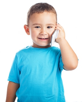 Child smiling with a phone in his ear