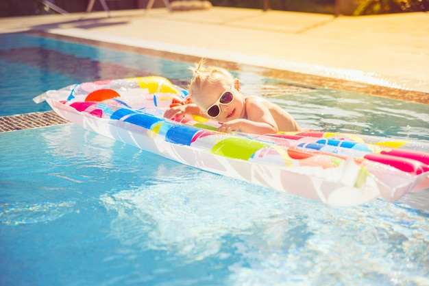 The child splashes on an inflatable colorful mattress in the pool.