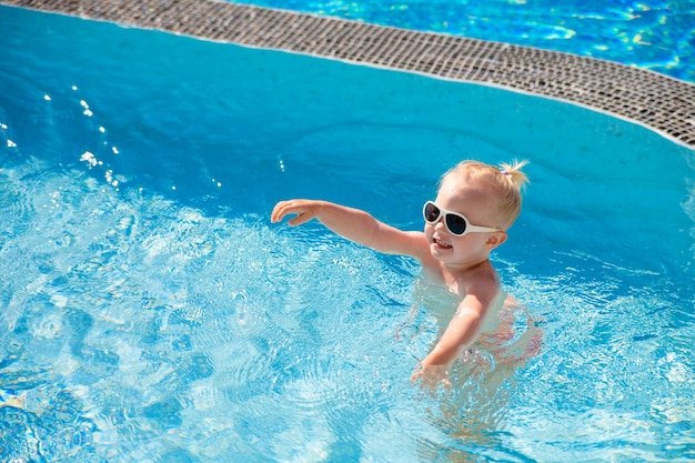 The child splashes in the pool with clear water in the summer illuminated by the sun.