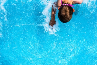 Child splashing in the cool water of a pool in summer