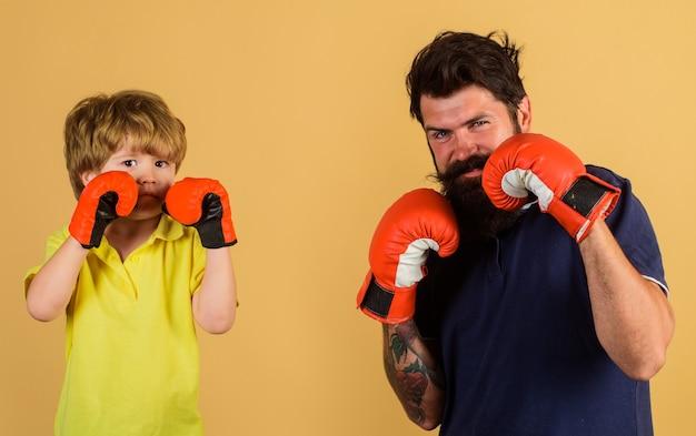 コーチとボクシングトレーニングで子供のスポーツマン。スパーリングの準備ができました。ボクシングの小さな男の子をコーチするひげを生やしたスポーツ男。