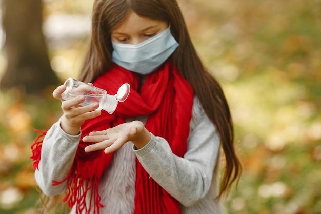 가 공원에 서있는 아이. 코로나 바이러스 테마. 빨간 스카프에 소녀입니다. 아이는 antiseptick을 사용합니다.